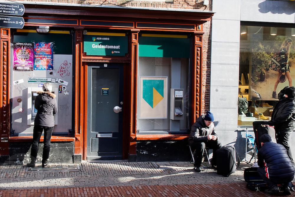 In Utrecht maken straatmuzikanten zich klaar om te spelen en geld te verdienen, terwijl een vrouw geld pint bij een automaat.<br /> <br /> In Utrecht streetmusicians are preparing themselves for playing, while a woman is getting money at the ATM.