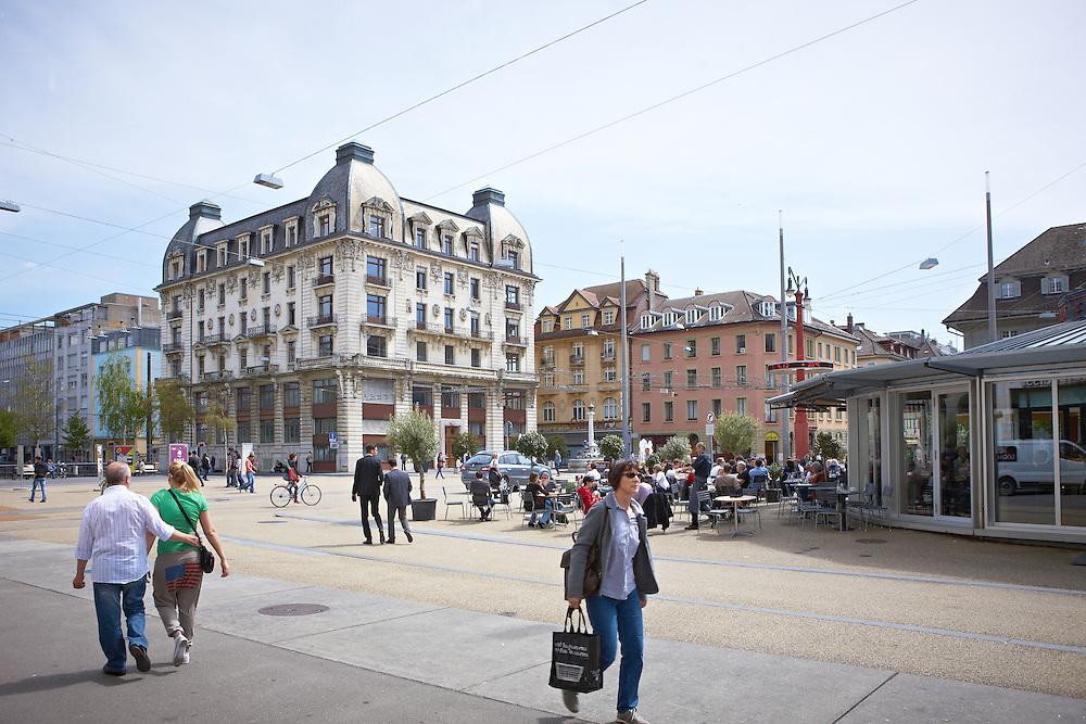 Passenten auf dem Zentralplatz in Biel. Frau mit Einkaufstasche, Paar und Junge Geschäftsläute überqueren den Platz. Café Arcade und Kontrollgebäude im Hintergrund
