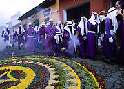 Holy Week. The cucuruchos, thousands of penitents in deep purple robes accompanies daily religious processions. The most spectacular Holy Week throughout Latin America, a sort of time machine to find an ancient Spain, where roman soldiers with the faces of Maya peasants interpret for days a choral rite alive in the collective memory as a matter of chronicle. In theatrical scenery of Antigua, between colonial palaces and Baroque churches uncovered by frequent earthquakes and eruptions of nearby volcanoes, processions come one after the other in an increasingly spasmodic crescendo until Holy Friday. From dawn to sunset for thousands of penitents, curucuchos rigorously dressed in purple, is a privilege, often passed down from father to son, to load on the shoulders heavy groups of statues with Jesus Christ, God, the Holy Spirit and the Virgin Mary.