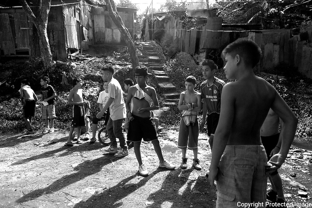 A group of boys gather in the streets of one of the slums in Alajuelita for a gmae of marbles.