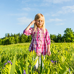 A young girl explores a field in Epping, New Hampshire.
