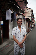 A man in his pajamas. Shanghai is famous for its residents wearing pajamas on the street, much as north Americans might wear a sweat suit.