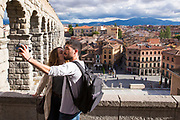 Tourist couple taking selfie photographs with SLR camera at famous spectacular Roman aqueduct, Segovia, Spain