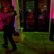 A couple celebrates, kissing and embracing, lit up by police lights on U street in Washington DC after Barack Obama was announced the winner of the 2012 presidential elections.