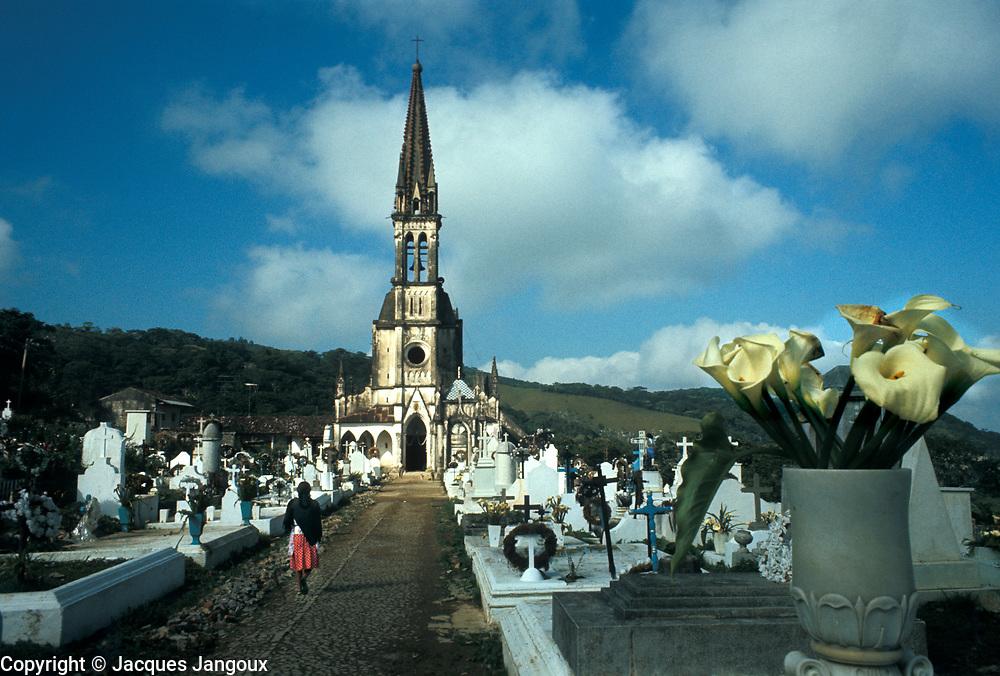 Lone woman walking through church ((Santuario de Nuestra Señora de Guadalupe; Iglesia de los Jarritos) cemetery, Cuetzalan, Puebla State, Mexico