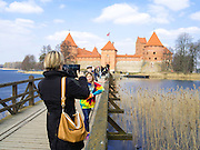 Tourists posing for the camera. View of Trakai Castle, Trakai, Lithuania, an old, restored historic castle that is famous in Lithuania.