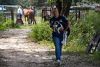 Ann-Margerat Johnston, who serves on the Georgia state council of the HSUS, carries a dog during a raid on a puppy mill in Johnston, SC on Tuesday, Sept. 11, 2012. HSUS workers found over 200 dogs, nine horses and 30-40 fowl. (770-205-2221)