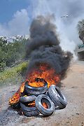 Burning tyres. Tyres are burnt as part of a demonstration to block roads and draw attention to the protest