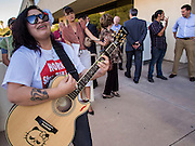 17 OCTOBER 2013 - PHOENIX, AZ:  VANESSA VARELA plays guitar and sings during a protest at the office of the Arizona Attorney General. About 100 people came to the office of Arizona Attorney General Tom Horne to protest the decision by Horne to sue community colleges in Maricopa County that charge DREAM Act students who are residents of Arizona out of state tuition rather than in state resident tuition. Nearly 10 people were arrested in a planned civil disobedience during the protest.   PHOTO BY JACK KURTZ