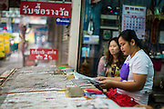 04 JANUARY 2012 - BANGKOK, THAILAND:   A lottery ticket seller waits for customers in a lottery shop along Sukhumvit Soi 77 in Bangkok. About 20 million Thais, nearly ? of the country's 65 million people, play lottery type games. The lotteries were brought to Thailand two hundred years ago by Chinese immigrants. Lottery agents are usually friends who collect bets but do not ask for money before the drawing. The lottery shops are close to Wat Mahabut and many people go the temple to see the fortune tellers and pray at the shrines there for guidance on the numbers to play in the lottery games.  PHOTO BY JACK KURTZ