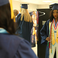Palace Roby uses a mirror backstage as she prepares for graduation withh her Nettleton classmates on Saturday morning.