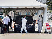 "26 APRIL 2020 - DES MOINES, IOWA: Medical workers conduct tests for COVID-19 at the first drive through testing site in Iowa. Iowa started mass testing Saturday, with a drive through testing site in a parking lot in downtown Des Moines. The testing this weekend is considered a ""soft opening"" for the program and tests were reserved for medical professionals and first responders. Despite numerous outbreaks in meat packing plants throughout Iowa, members of the public have not been able to get tested. On Saturday, 25 April, there were 5,092 confirmed cases of COVID-19 (Coronavirus / SARS-CoV-2) in Iowa (an increase of 647 since Friday, April 24) and 112 deaths in Iowa caused by COVID-19.          PHOTO BY JACK KURTZ"