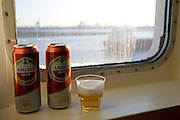 Two Amstel beer cans and glass by ship porthole