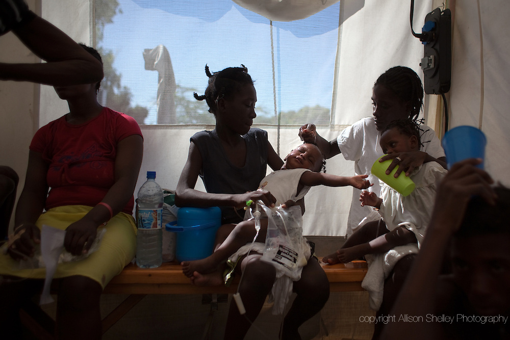 A pair of 15-month-old twins with cholera are held by their mother, right, and sister, center, as they receive IV drips in the intake tent at a cholera clinic set up by Medecins Sans Frontieres in the Tabarre neighborhood of Port-au-Prince, Haiti, November 19, 2010.