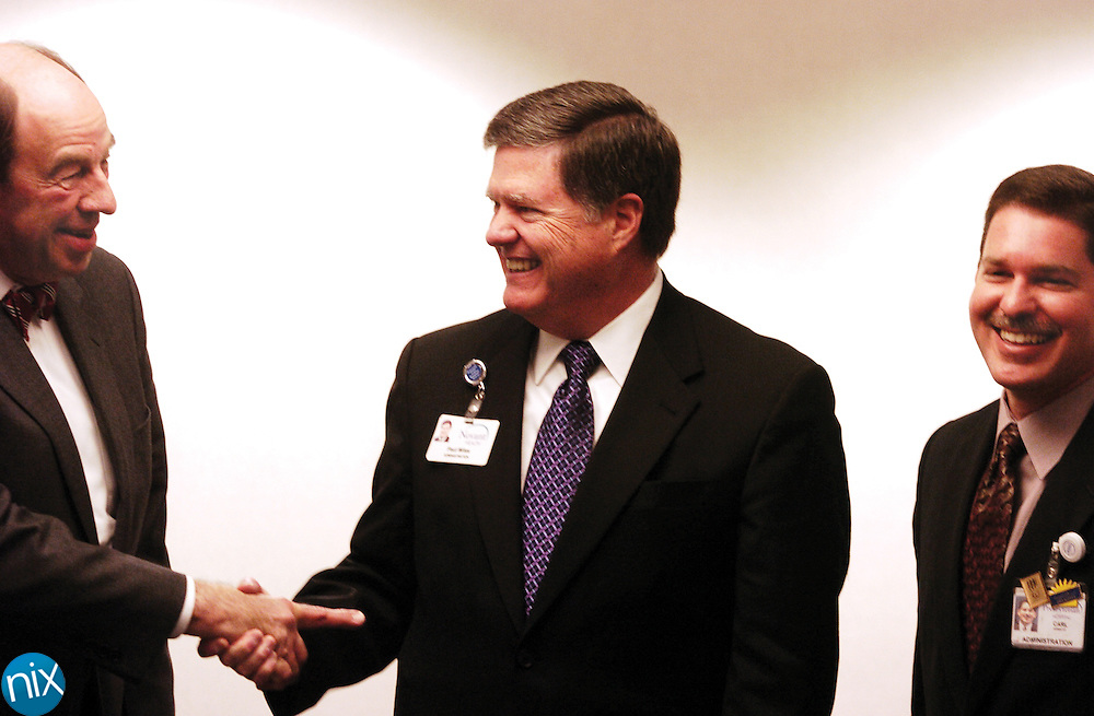 Glenn Ketner, chairman of the Rowan Regional Board of Directors, shakes hands with  Paul Wiles, CEO of Novant Health, Wednesday morning at a press conference announcing the official merger of the two health care providers. Next to Wiles is Carl Armato, president of Presbyterian Healthcare.
