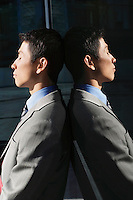 Businessman Leaning Against reflective Wall outside profile