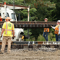 A BNSF work crew works on the rails at Spring Street behind the Tupelo Farmers Depot replacing sections of old rails on Monday morning.