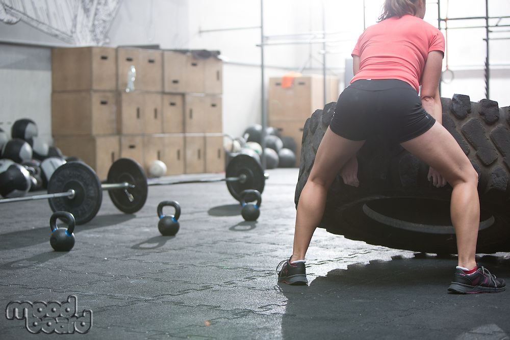 Rear view of woman flipping tire in crossfit gym