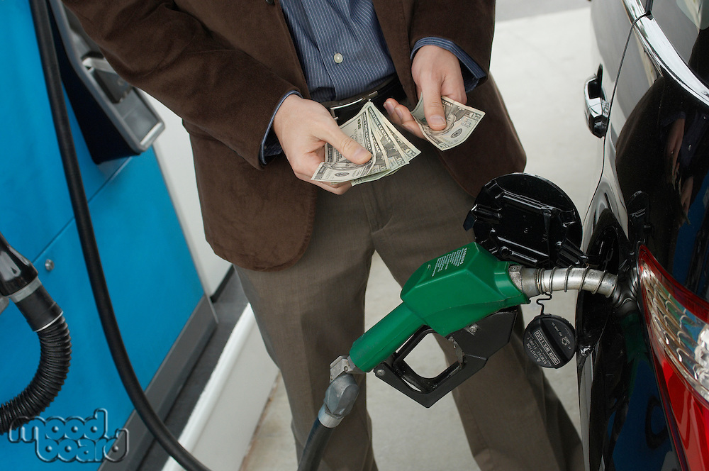 Man counting money over gas pump in car, mid section