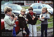 Boys & girl hold puffin chicks they rescued night before on Heimaey streets to free to shore Iceland