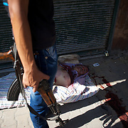 August 14, 2012 - Aleppo, Syria: A Free Syria Army (FSA) fighter stands beside the body of a civilian killed minutes earlier during a attack by the regime war plane against a local hospital in Tariq Al-Bab neighborhood in central Aleppo. The Syrian Army have in the past ten days increased their attacks on residential neighborhoods where Free Syria Army rebel fights have their positions in Syria's commercial capital, Aleppo. (Paulo Nunes dos Santos/Polaris)