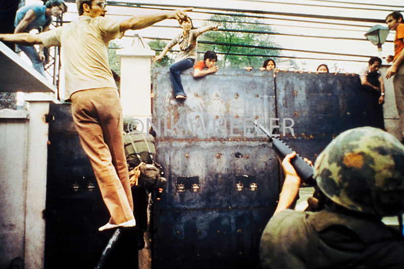 Vietnamese try to scale wall of US Embassy to escape North Vietnamese troops entering Saigon during evacuation of Americans at the Fall of Saigon, last day of US involvement in the Vietnam War