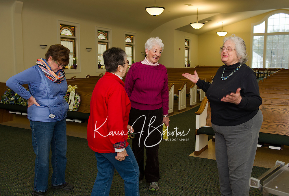 """The """"flower committee"""" Judy Robertson, Penny Franciosi, Sandra Stafford and Jane Rollins decorates the Gilford Community Church Friday morning for Easter services on Sunday.  (Karen Bobotas/for the Laconia Daily Sun)"""