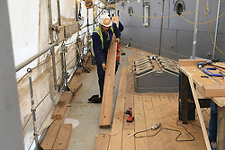 Photo/Paul McErlane© Licensed to London News Pictures. 28/04/2016. Belfast County Antrim, Northern Ireland, UK. HMS Caroline's restoration is the biggest World War One project of the century. Funded by Heritage Lottery Fund and supported by DETI, the Portsmouth-based National Museum of the Royal Navy undertook the restoration project three years ago. It will be completed in time for the centenary of the Battle of Jutland on May 31 2016. A workman lays fresh decking to the World War One ship. Photo credit : Paul McErlane/LNP