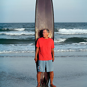A man in his early seventies stands next to a longboard on Wrightsville Beach, NC.
