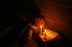 April 25, 2017 - Gaza City, The Gaza Strip, Palestine - A Palestinian refugee girl is studying candles in her family's temporary home during the power outage in the Jabalya refugee camp in the northern Gaza Strip, 25 April 2017. Most Palestinians in the Gaza Strip use batteries, generators and candles to illuminate their homes. Gaza residents, who live in about 1.8 million people, live about 20 power cuts a day. According to reports, the only Gaza Strip operating on 16 April 2017 ran out of fuel and stopped work. (Credit Image: © Mahmoud Issa/Quds Net News via ZUMA Wire)