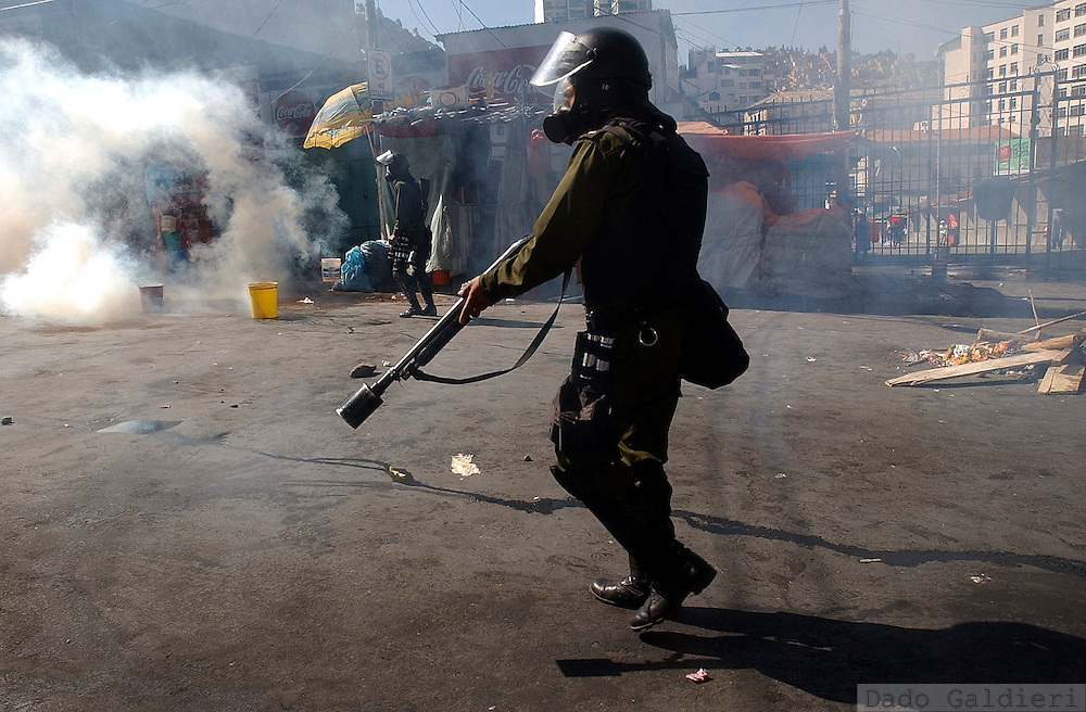 A riot police officer holds his position during clashes against a demonstrator in La Paz, Bolivia on Tuesday, June 7, 2005. A resignation offer by President Carlos Mesa, whose 19-month-old free-market government was unraveling, did little to halt a crippling blockade of the Bolivian capital, as demonstrators marched on La Paz for a second day Tuesday to demand more power for Bolivia's poor Indian majority.(Dado Galdieri)