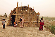 Marshland Arabs in Maysan Province, Iraq outside of a hut they live in are visited my American soldiers on patrol