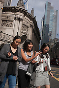 Young Asian women walk along Bishopsgate on 12th September, in the City of London, UK.