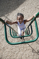 Girl (7-9) climbing jungle gym
