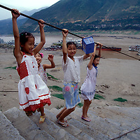 China, Hubei Province, Wushan, Girls play on boat cable above Yangtze River