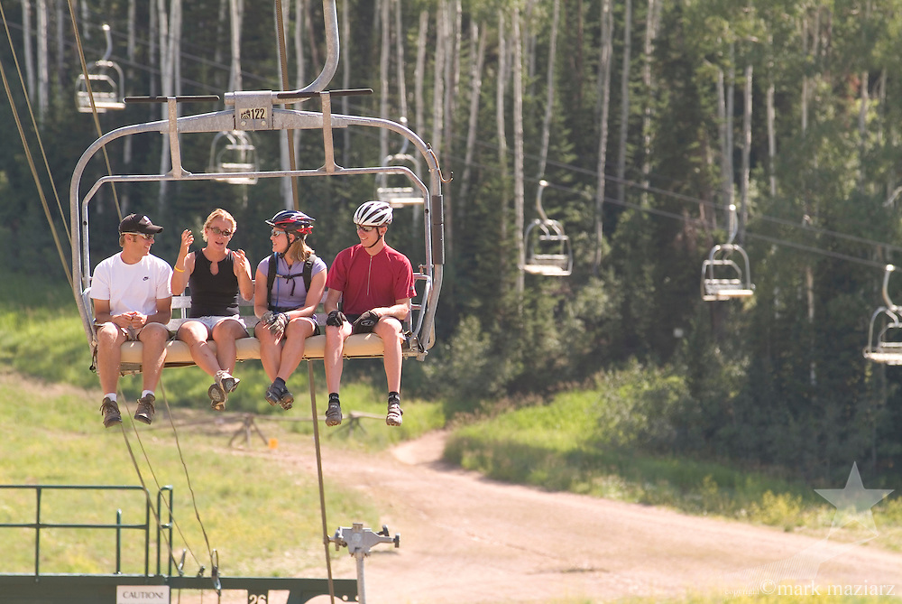 4 people riding on lift in summer at Deer Valley Resort, Park City, Utah USA