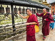 31 JULY 2015 - KATHMANDU, NEPAL: Buddhist monks spin prayer wheels around Swayambhunath Stupa, a large Buddhist stupa in Kathmandu. Parts of the stupa were badly damaged in the Nepal earthquake of 2015 but it is still open for religious devotees and tourists. Construction of the stupa started in the 1600s.    PHOTO BY JACK KURTZ