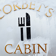 The snow covered sign into Corbet's Cabin at the top of JHMR.