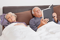 Elderly man reading book while spouse sleeping besides in bedroom