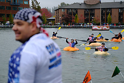 Police officers race firefighters in giant carved-out pumpkins during the 14th annual West Coast Giant Pumpkin Regatta in Tualatin, Ore. on October 21, 2017. (Photo by Alex Milan Tracy)