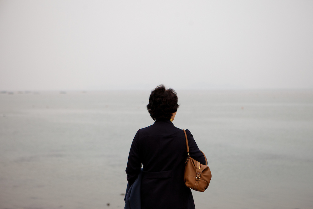 "Woman watching the already closed  ""Mysterious Sea Road"" at Hoedong shore (Jindo island) which is usually for about one and a half hour fully open. Jindo is the 3rd biggest island in South Korea located in the South-West end of the country and famous for the ""Mysterious Sea Route"" or ""Moses Miracle"" . Every spring thousands flock to the shores of Jindo to walk the mysterious route that stretches roughly three kilometers from Hoedong to the distant island of Modo. Materializing from the rise and fall of the tides, the divide can reach as wide as forty meters."