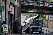A garage worker from an MoT testing centre and the damaged aftermath of a lorry at Loughborough Junction after it crashed into one of the railway bridges - a main transport route for commuters into the City, on 8th May 2018, in south London, England. One person was injured.
