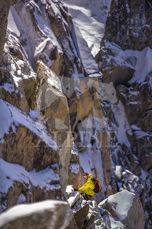 A male mountaineer as seen on a sunny day climbing Cosmiques ridge, on the South face of Aiguille du Midi, Chamonix, France.