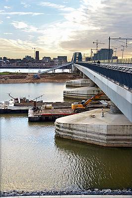 Nederland, Nijmegen, 23-11-2015 De 4km. lange nevengeul aan de overkant van de Waal bij Lent nadert zijn voltooiing. Laatste werkzaamheden. Grootste onderdeel van de vele werken van Rijkswaterstaat om bij hoogwater een betere waterafvoer in de rivier te hebben. In precies drie jaar is het werk uitgevoerd. Het is een omvangrijk project waarbij onder meer de pijlers van het spoorviaduct een bredere basis kregen omdat die straks in de loop van het water staan. Het dorp veurlent komt op een kunstmatig eiland te liggen met twee bruggen als ontsluiting. Een voetgangersbrug en een andere, de Promenadebrug, voor normaal verkeer. Inmiddels begint de nieuwe kade aan de noordkant van deze geul vorm te krijgen. Ruimte voor de rivier, water, waal. In de nieuwe dijk is een drempel gebouwd die stapsgewijs water doorlaat en bij hoogwater overloopt. The Netherlands, Nijmegen Measures taken by Nijmegen to give the river Waal, Rhine, more space to flow during highwater and to prevent the risk of flooding. Room for the river. Reducing the level, waterlevel. Large project to create a new paralel gully, an extra flow of water, so the river can drain more water during highwater. Due to climate change and expected rise, increase of the sealevel, the Dutch continue to protect their land from the water. Foto: Flip Franssen/HH