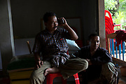 Supot Kalasong, 42, sits on the floor next to a member of the Southern Peasant Federation of Thailand who lives outside the community. Mr Supot was shot in April 2016 but survived.<br /> <br /> Since 2008, Klong Sai Pattana community of around 70 families have been embroiled in a conflict with a palm oil company that locals allege has been trying to violently evict them. Since 2010, four members of the community have been shot dead and a fifth shot, but survived.<br /> <br /> For decades the palm oil company Jiew Kang Jue Pattana Co., Ltd has illegally occupied and cultivated palm oil trees on a 535-acre plot of land in the Chai Buri District of Surat Thani Province. <br /> <br /> The company operated with no official legal documentation or land concession, until the Southern Peasant's Federation of Thailand (SPFT), who supports the community, began investigating them and collecting evidence.<br /> <br /> This evidence ultimately lead to a Supreme Court ruling against the company for illegal trespassing and land encroachment. But the community still struggles to remain on the land to this day with the last shooting happening in April 2016, years after the court case was won.