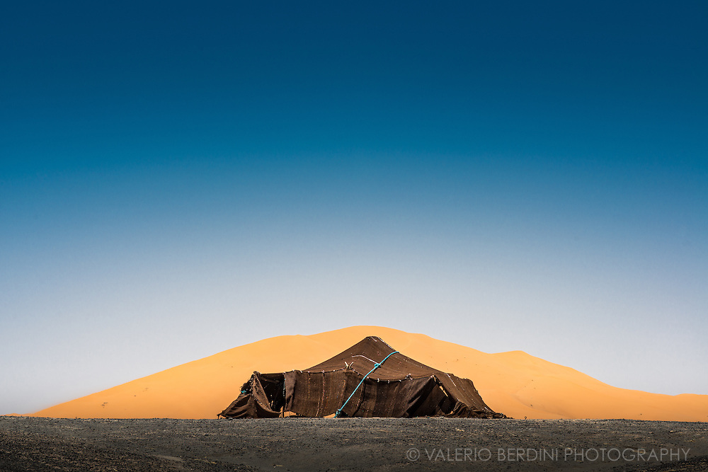 "A berber tent put up in the black desert in front of one of the giant sand dunes of Erg Chebby, near Merzouga in the Moroccan Sahara at the border with Algeria on May 2015. Berbers call ""black desert"" the darker volcanic ground to differentiate it from the sandy dunes."