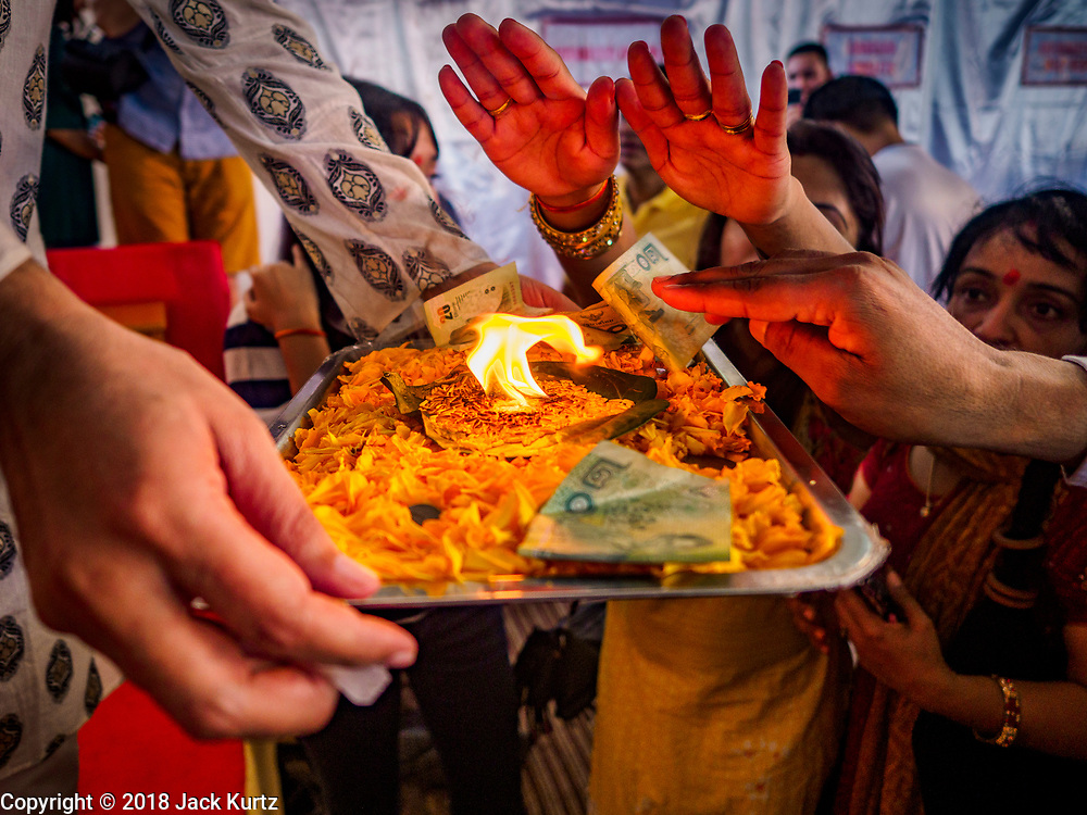 """23 SEPTEMBER 2018 - BANGKOK, THAILAND: People pray and makes offerings at the Ganesha Festival at Wat Dan in Bangkok. Ganesha Chaturthi also known as Vinayaka Chaturthi, is the Hindu festival celebrated on the day of the re-birth of Lord Ganesha, the son of Shiva and Parvati. The festival, also known as Ganeshotsav (""""festival of Ganesha"""") is observed in the Hindu calendar month of Bhaadrapada, starting on the the fourth day of the waxing moon. The festival lasts for 10 days, ending on the fourteenth day of the waxing moon. Outside India, it is celebrated widely in Nepal and by Hindus in the United States, Canada, Mauritius, Singapore, Thailand, Cambodia, and Burma.   PHOTO BY JACK KURTZ"""