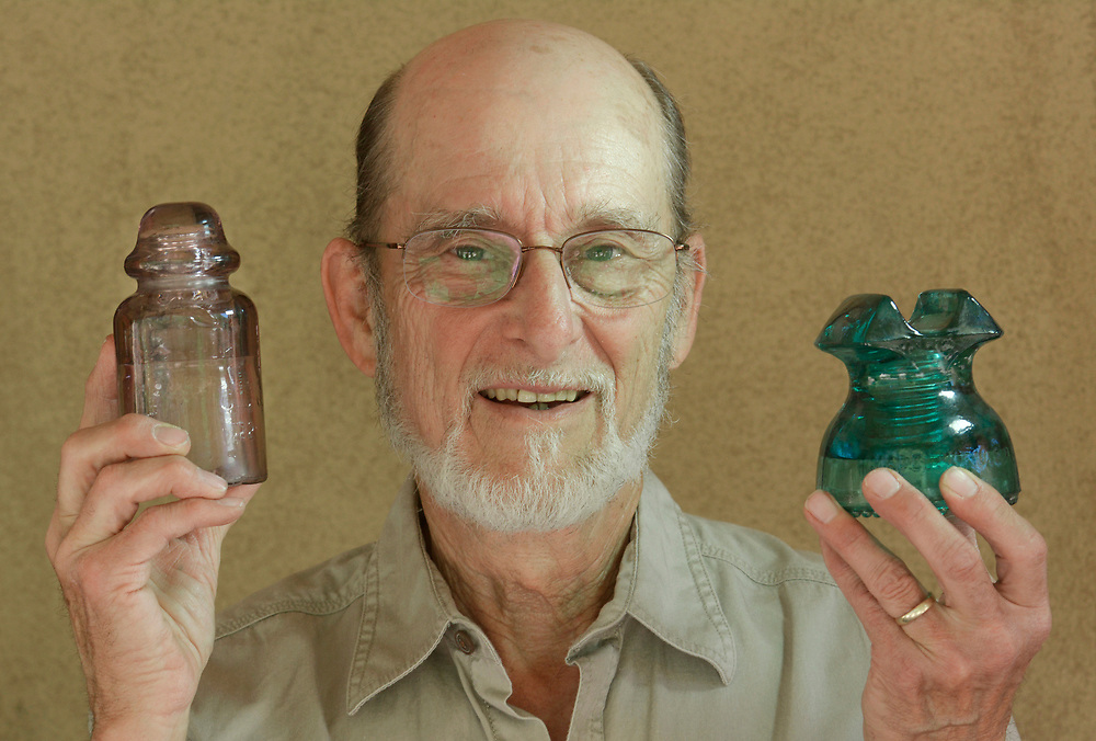 gbs050417h/LIVING -- Tom Katonak of Corrales holds an Australian glass telephone insulator from the 1940's, which turned a light amethyst color from UV rays, left, and a green 400 volt power insulator made by the Hemingray Glass Company from the 1930's , right. (Greg Sorber/Albuquerque Journal)