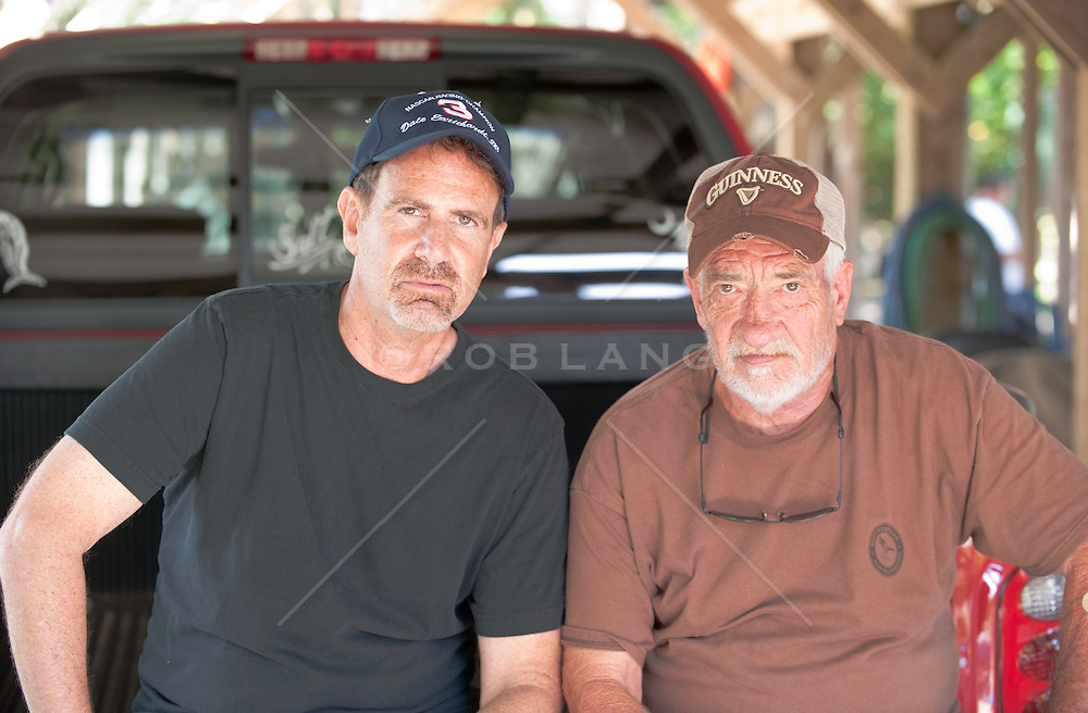Two Men in caps with attitude sitting on the back of a parked truck
