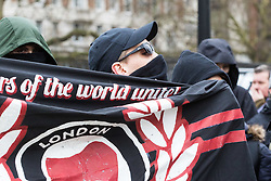 "Nationalist group Pro Great Britain hold a 'freedom of speech' protest at Hyde Park Corner with a small number of anti-fascists counter protesting. The demonstration comes after two speakers Austrian Martin Sellner and American Brittany Pettibone from Generation Identity, ""a Europe-wide patriotic youth movement that promotes the values of homeland, freedom and tradition through peaceful activism, political education, and community & cultural activities"" were refused entry to the UK by border officials. PICTURED: Masked anti-fascist protesters shout at their opponents from behind a banner. London, March 11 2018."